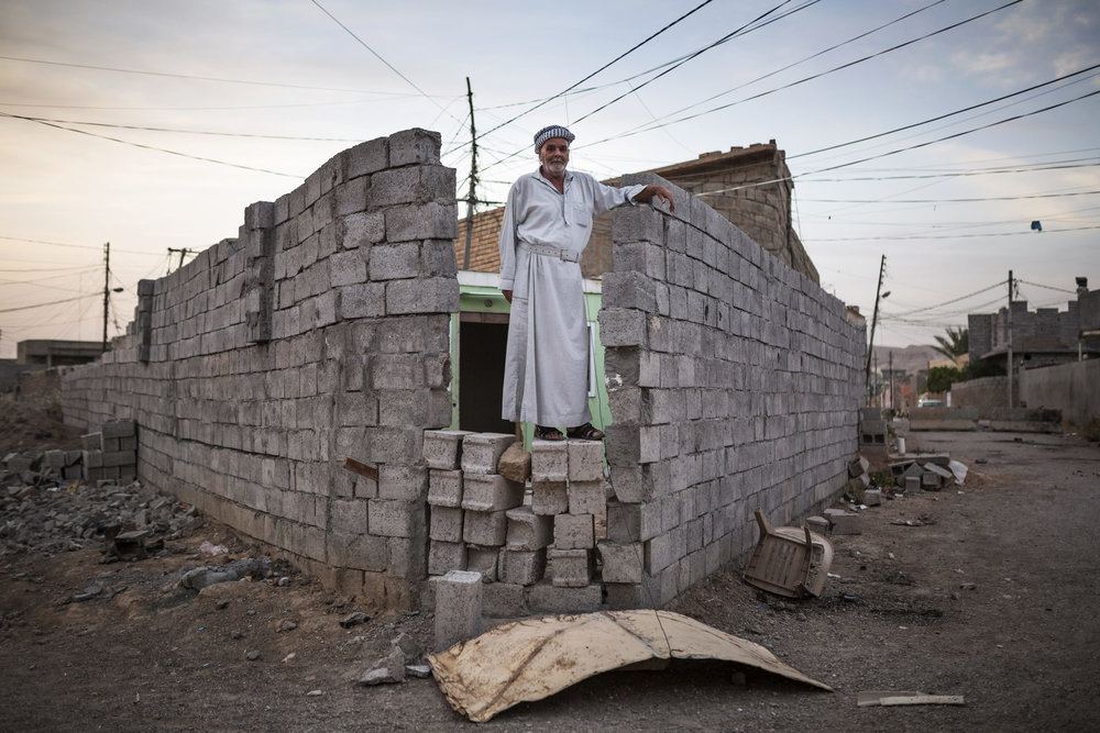 A man stands on a wall built to protect his property from clashes between Kurdish and Turkman forces.