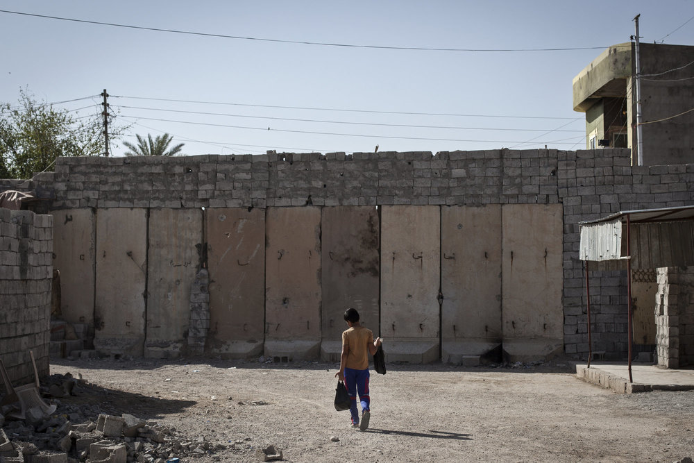 A wall across a main street separates Kurdish and Turkman districts.
