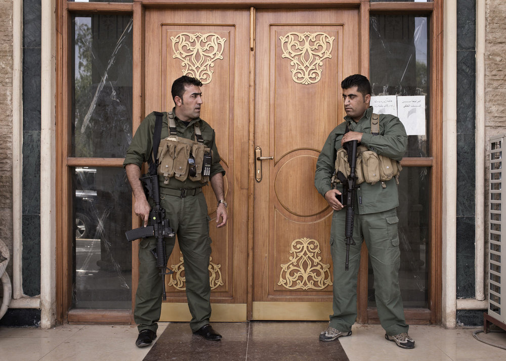 Kurdish security forces guard the entrance to the mayor's office.