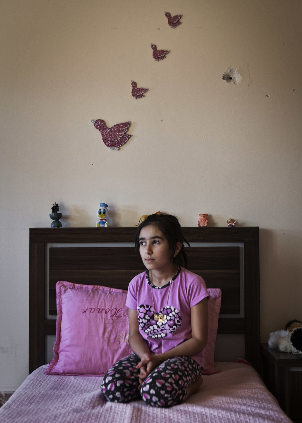 Maraj Emad, 12, sits beneath a bullet hole in her wall.