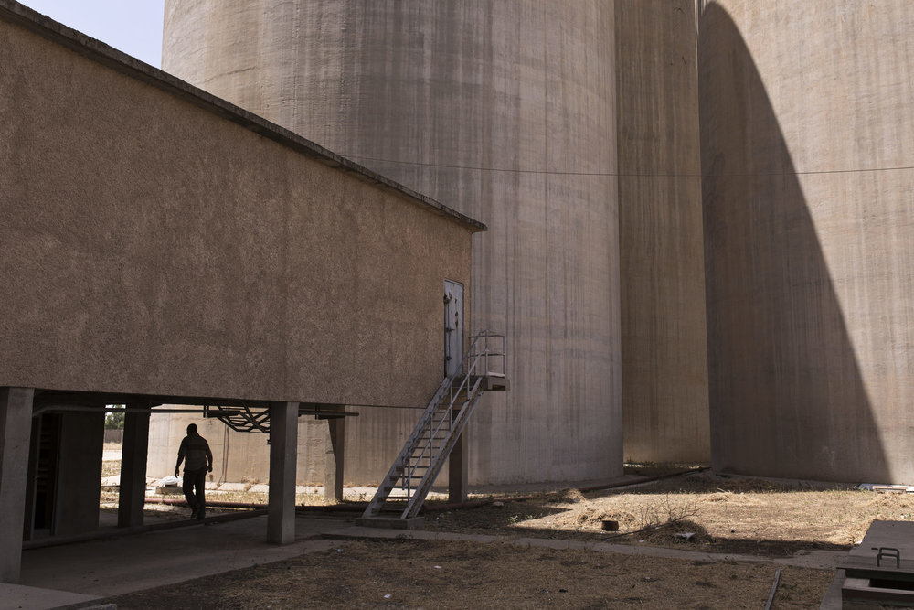 A man walks through the site of a grain silo.