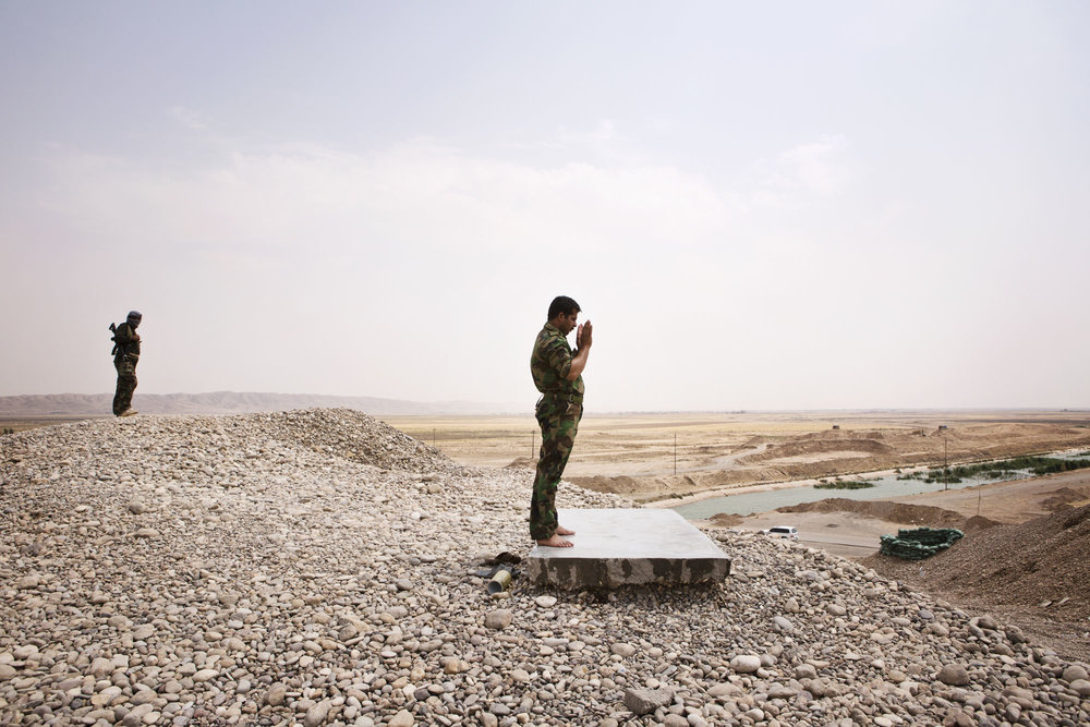 A Peshmerga prays at a front line position.