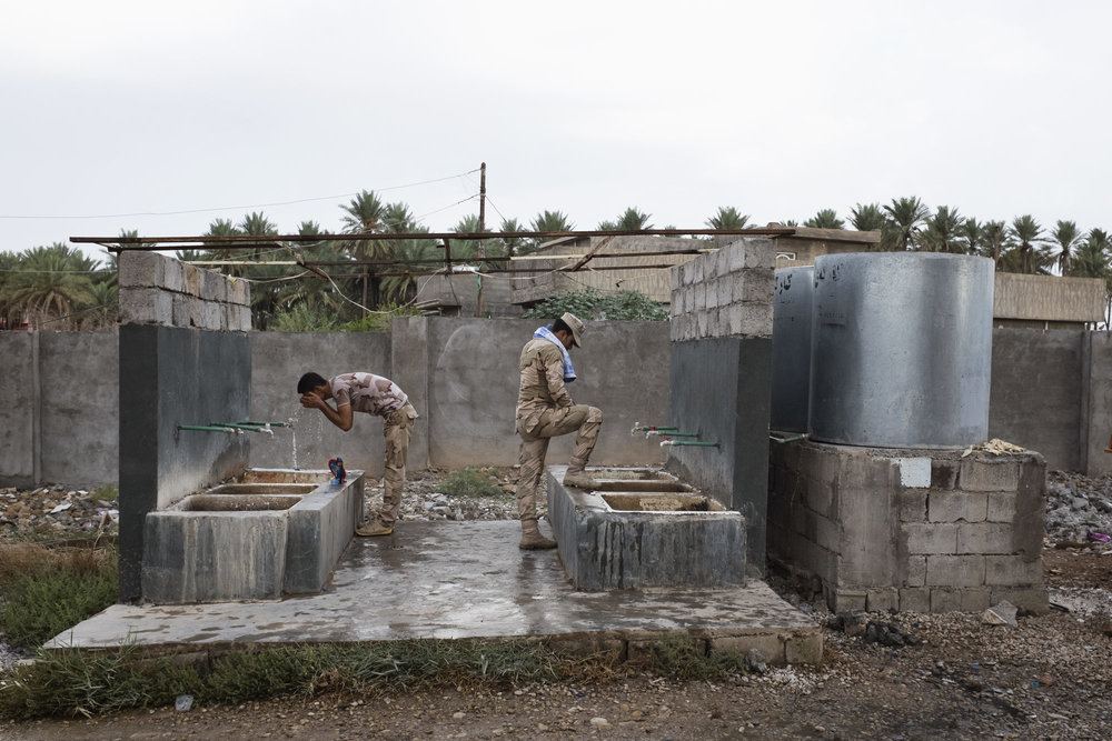 Peshmerga have a morning wash at a base.