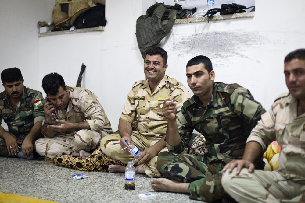 Peshmerga smoke, sing and play with their phones in the evening.