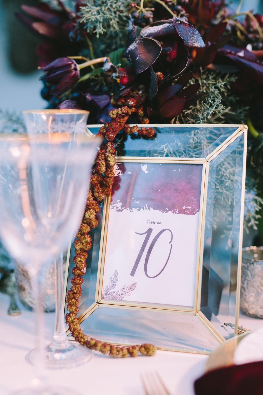 styled-shoot-winter-elatos-resort-greece-destination-wedding-table-luxury-chic-burgundy-white-gold-dinner-table-floral-design-glod-frame-table-number