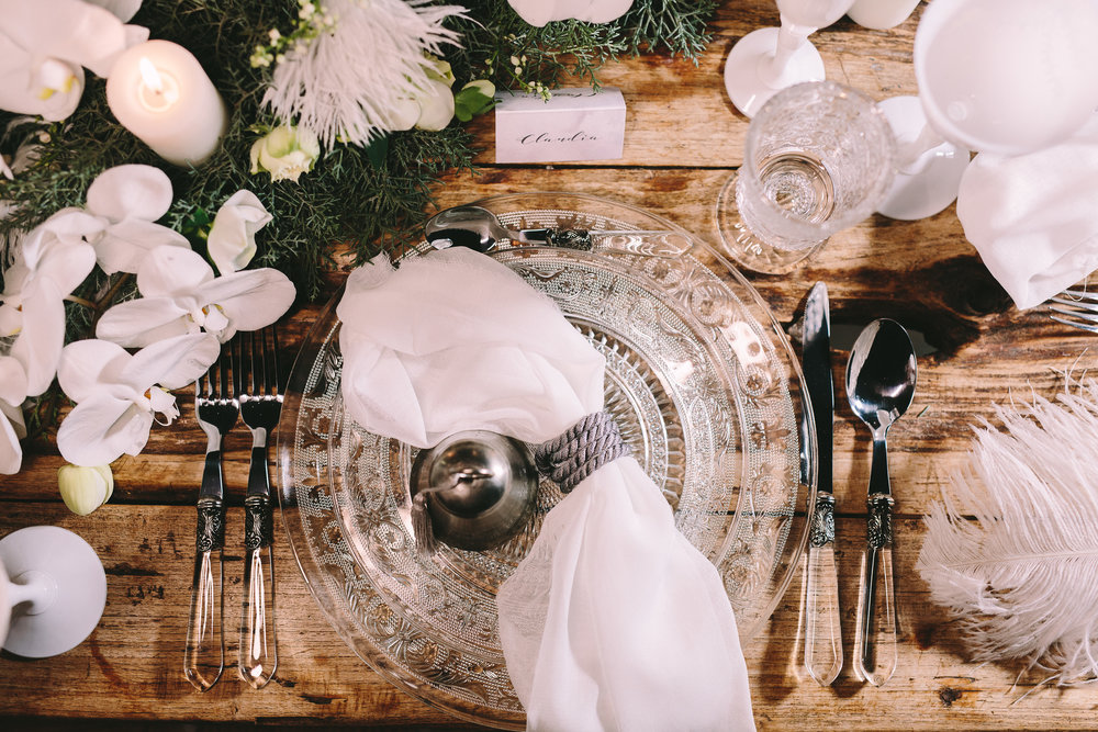 Destination-winter-wedding-greece-wedding-planning-snow-white-feathers-luxury-silver-cutlery-napkin-orchids-escortcards