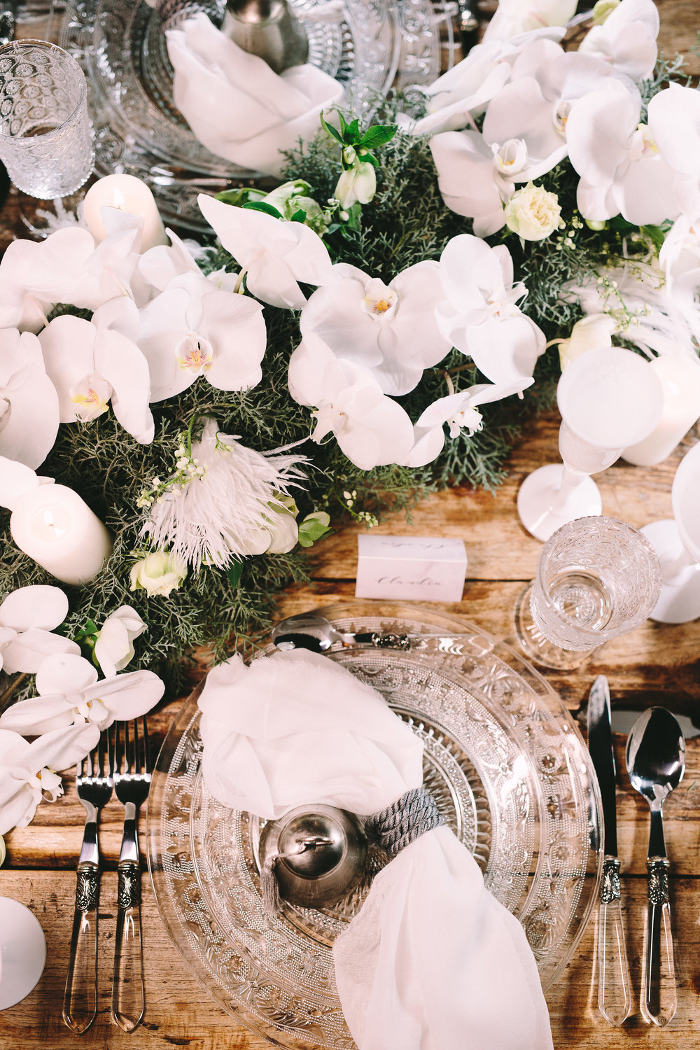 Destination-winter-wedding-greece-wedding-planning-snow-white-feathers-luxury-silver-cutlery-napkin-orchids-greenery-chic