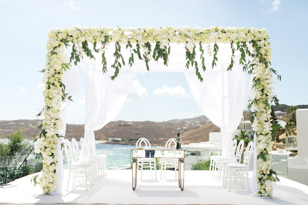 royal-myconian-resort-venue-galaxy-sunset-chuppah-chuppa-huppah-bridal-canopy-jewish-ceremony-floral-decoration-couple-bride-groom-event-planning-silkentile-greece