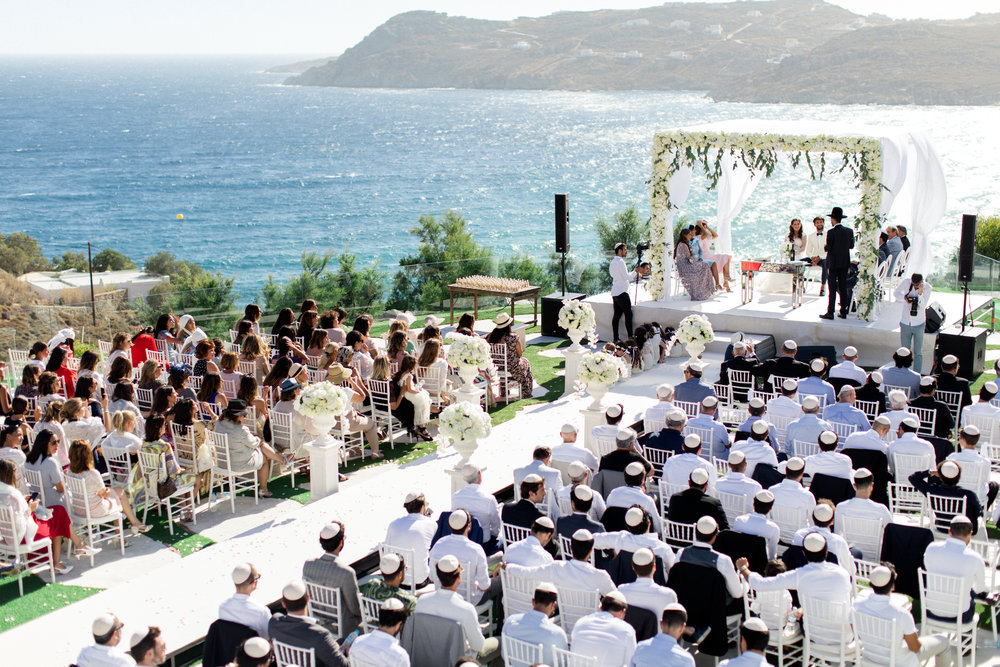 royal-myconian-resort-venue-galaxy-sunset-chuppah-chuppa-huppah-houppa-booklet-bridal-canopy-jewish-ceremony-kippah-hat-monograms-stationery-wedding-logo-floral-decoration-couple-bride-groom-event-planning-silkentile-greece
