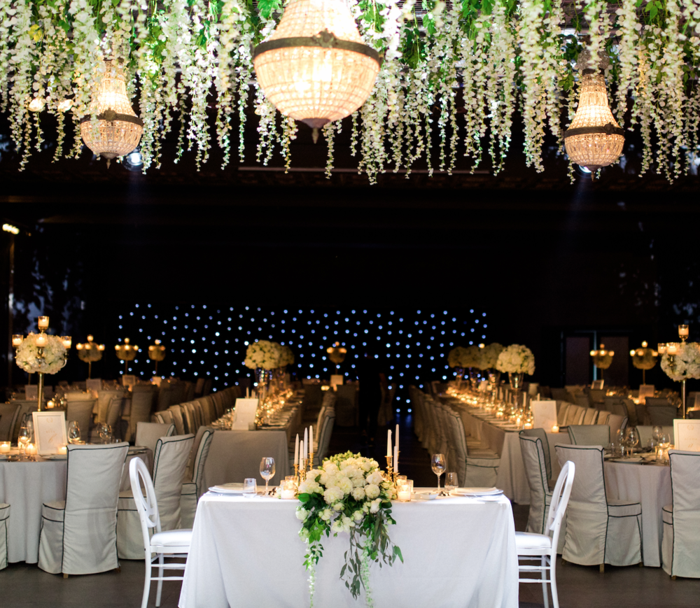 wedding-dinner-party-jewish-traditional-menu-luxury-event-decoration-hanging-wisteria-crystal-chandeliers-light-design-table numbers-table-arrangements-gold-candle-holder-event-planning-silkentile-destination-royal-myconian-delos-venue