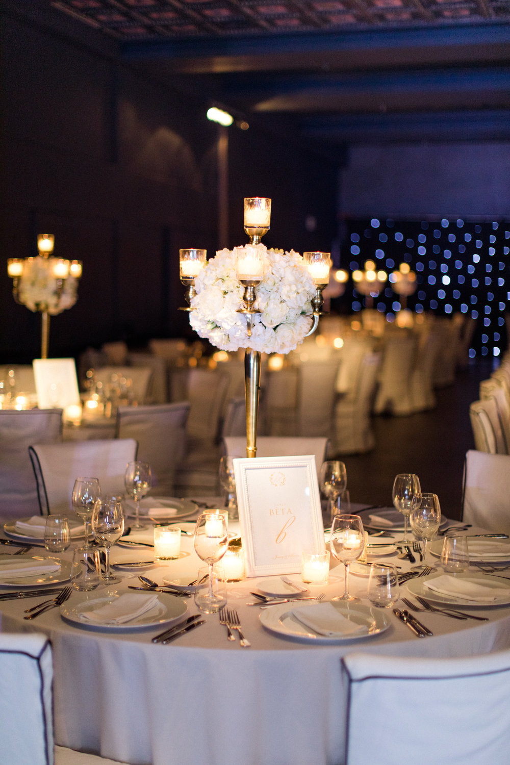 wedding-dinner-party-jewish-traditional-menu-luxury-event-decoration-hanging-wisteria-crystal-chandeliers-light-design-table numbers-table-arrangements-gold-candle-holders-event-planning-silkentile-destination-royal-myconian-delos-venue