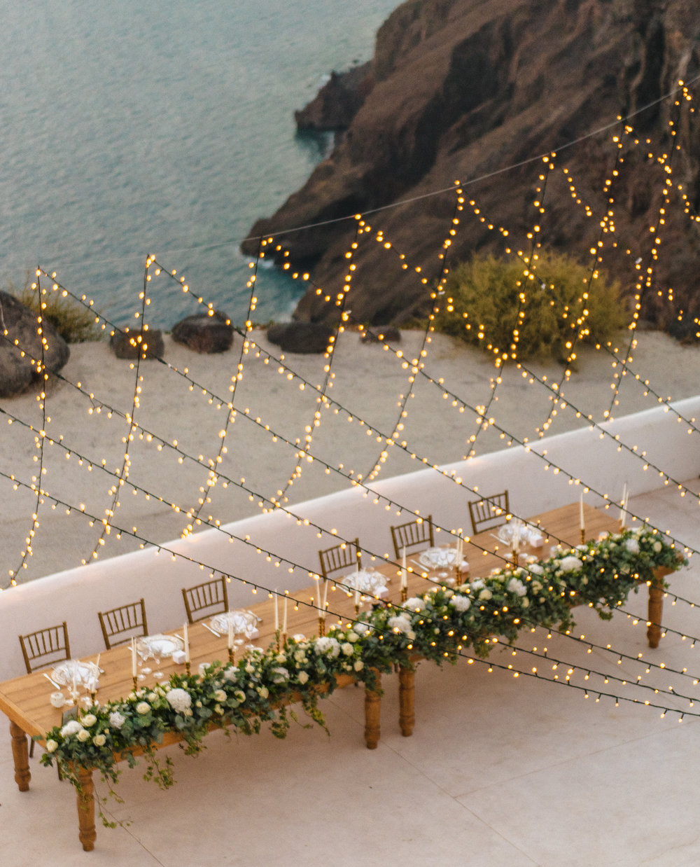 santorini-island-greece-wedding-dinner-celebration-ceremony-groom-brid-sunset-wedding-table-crystal-charger-plate-arrangement-mini-bulbs-rocabella-hotel-silkentile-event-planning-firm