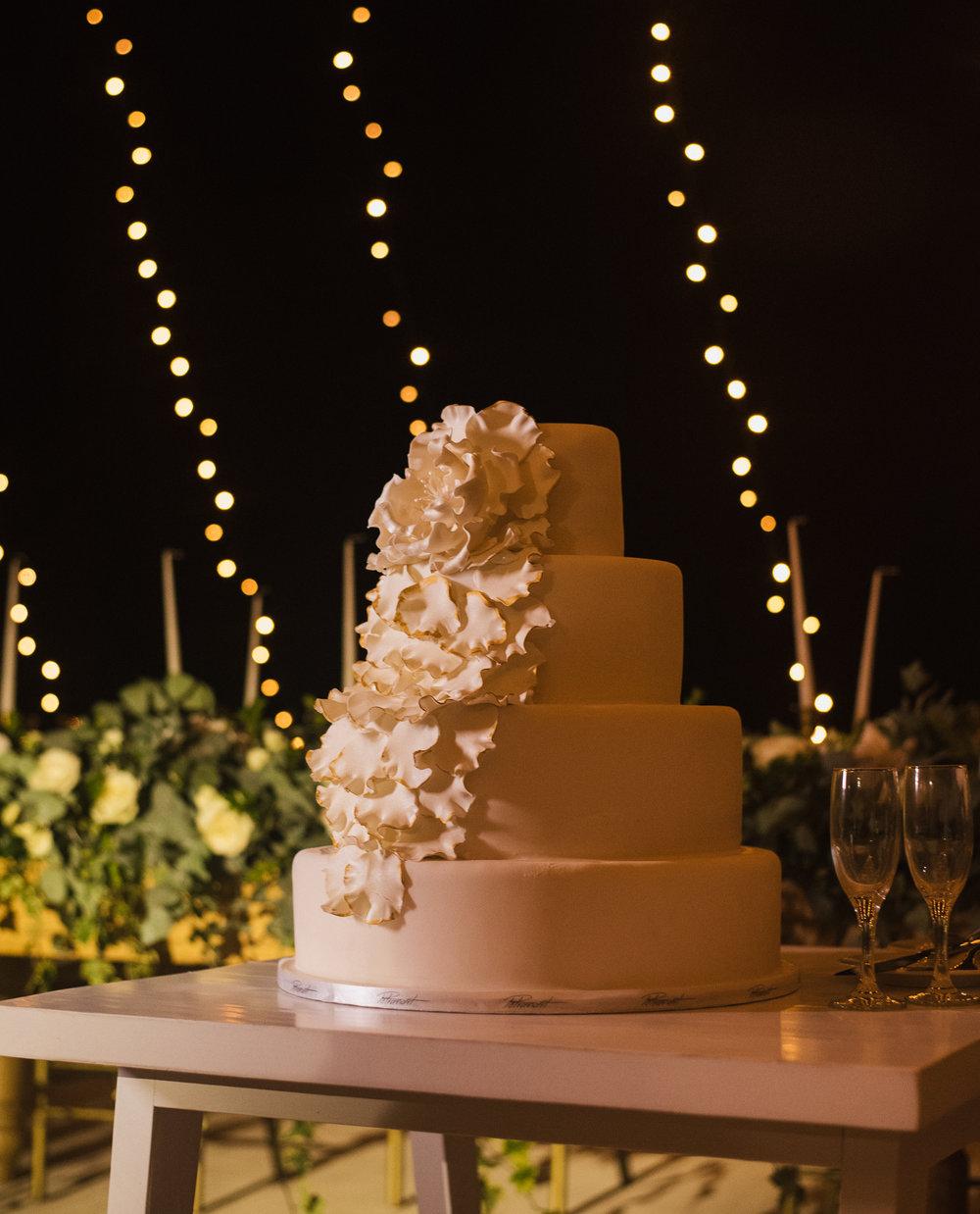 santorini-island-greece-wedding-dinner-celebration-groom-bride-sunset-wedding-table-crystal-charger-plate-flower-arrangement-dessert-table-naked-cake-decoration-fairy-lights-mini-bulbs-rocabella-hotel-silkentile-event-planning-firm