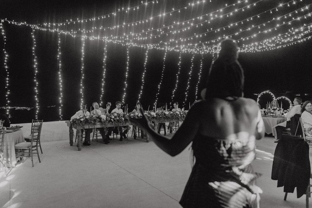 santorini-island-greece-wedding-dinner-celebration-ceremony-groom-bride-fairy-lights-bulbs-wedding-table-arrangement-rocabella-hotel-live-band-silkentile-event-planning-firm