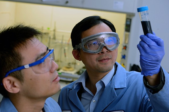 Image caption:Chao Wang (right) inspects a glass vial containing cobalt cores, each coated with a thin layer of platinum. At left is postdoctoral fellow Lei Wang.