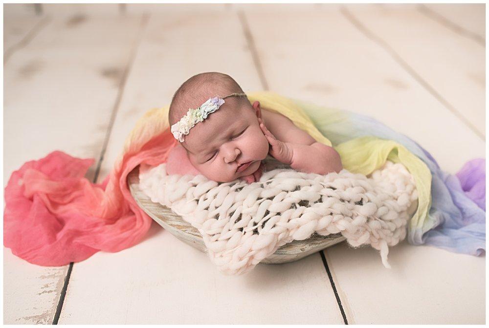 Columbus ohio newborn photographer rainbow baby girl with rainbow headband and wrap in prop