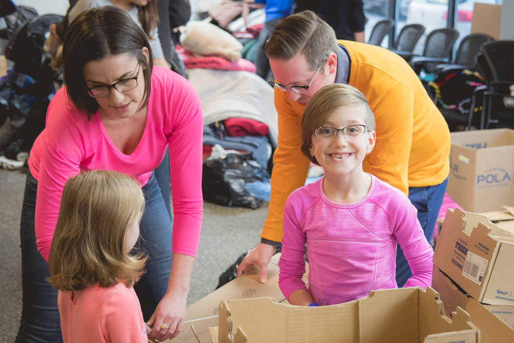 Krista, Mike and their daughters Olivia (5) and Alex (9) work at assembling boxes for food that will be transported downtown.
