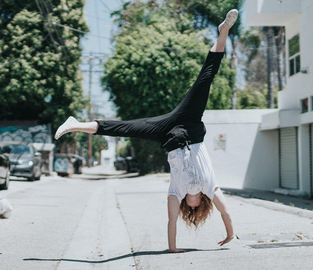 happy woman cartwheel outside on street