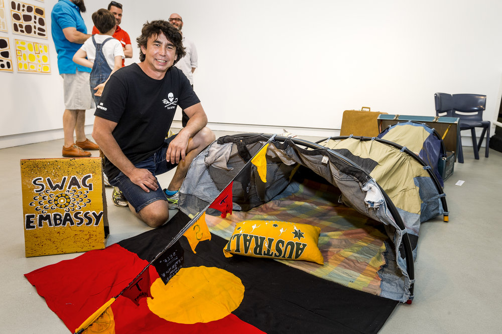 Christopher Burthurmarr Crebbin with his artwork Swag Embassy, installation view, Prospect Gallery, 2015. Photograph John Nieddu