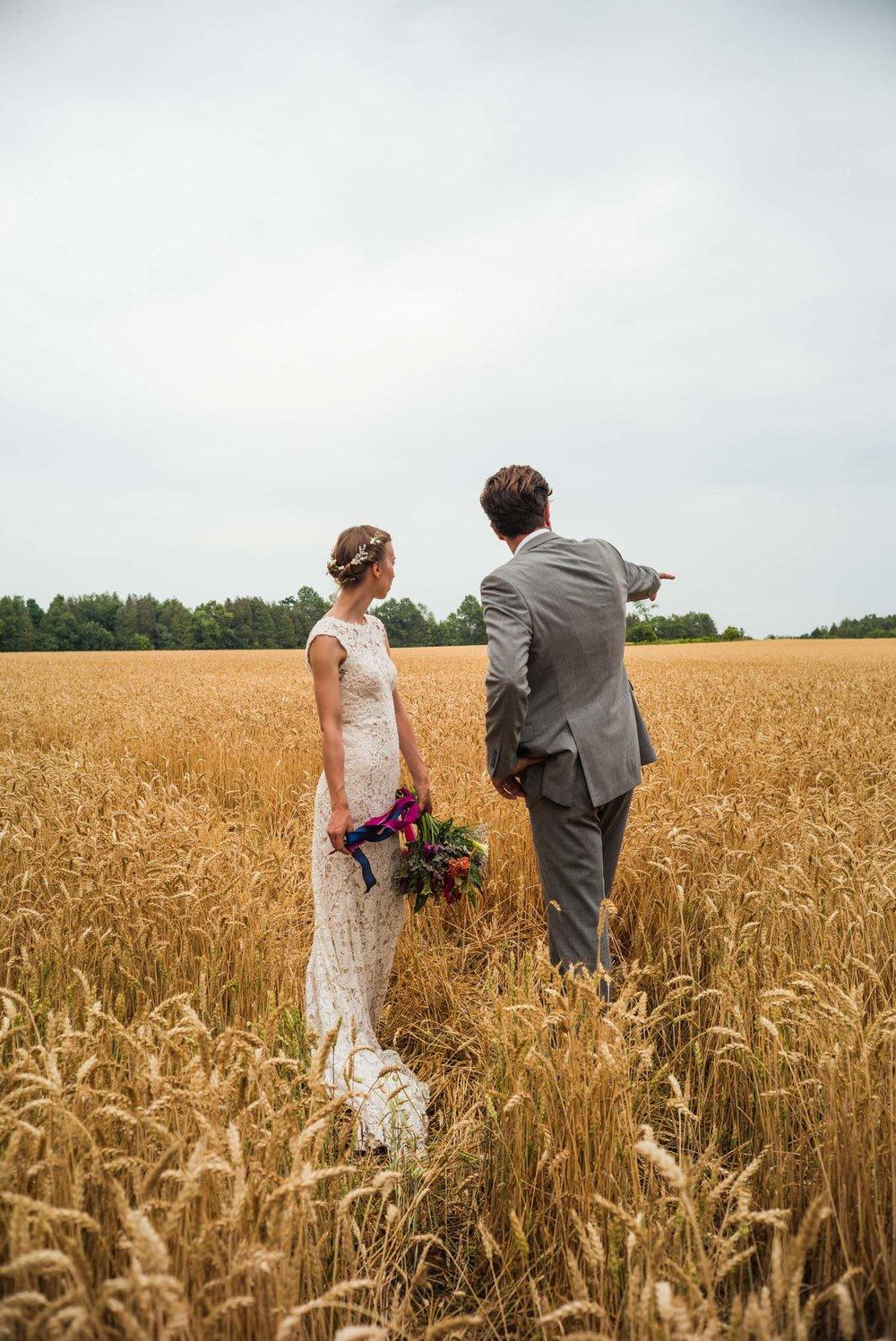 couple standing in a wheat field.jpg