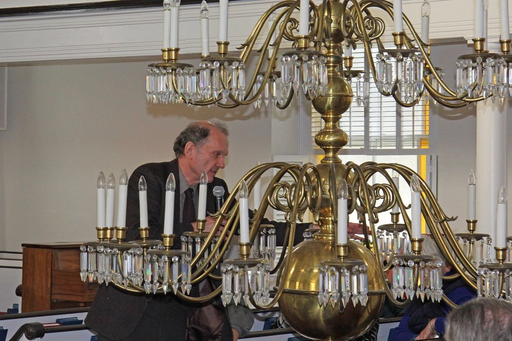 Roland Wilbur of the Antique Lighthouse in Philadelphia examines the historic chandelier during an informational meeting.