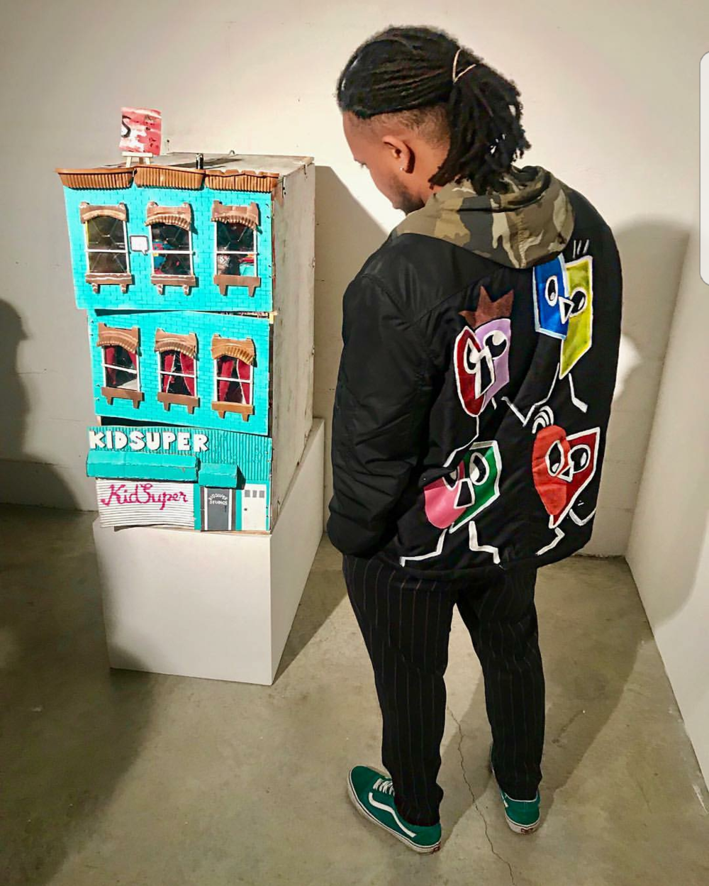Here is a photo of  Nicodex Dubois  (@niconoflaw) admiring KidSuper's model-replica of the studio and storefront located in Brooklyn. Nicodex is wearing a jacket designed by artist P-Studios James.