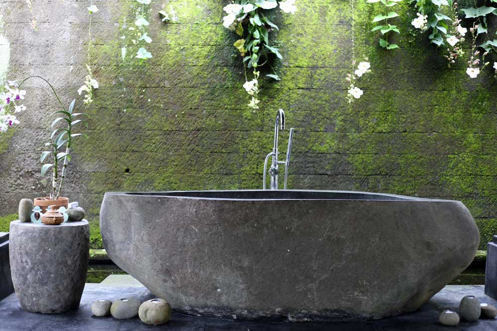 Casual outdoor bathtub with koi pond moat.