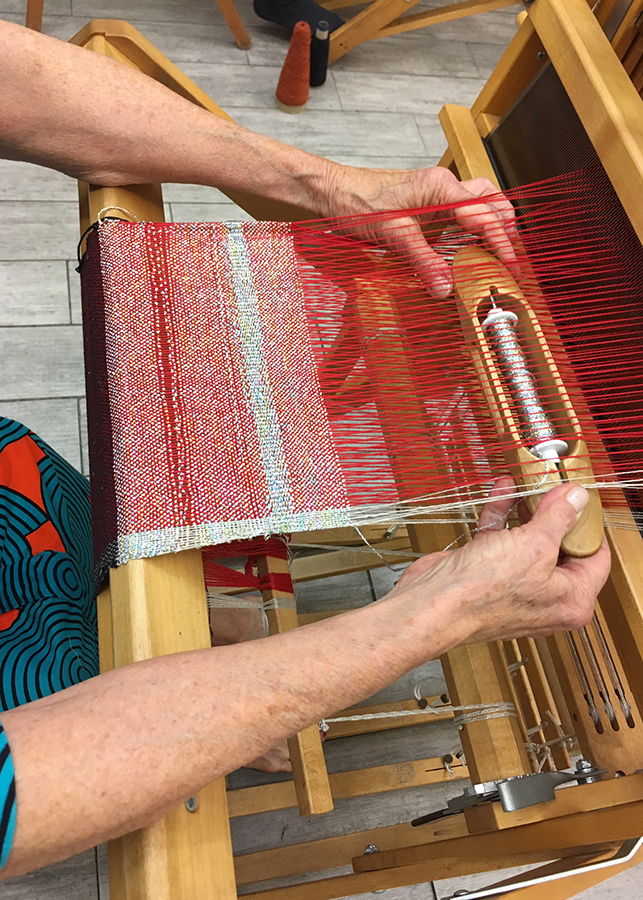 student weaving on a floor loom in Weaving 101 class at the Textile Arts Center, 2018