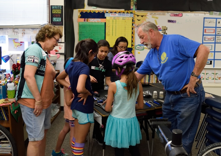 Kiwanis Bike Program's Roger Jacobson teaching Bike Like a Girl campers about bikes.