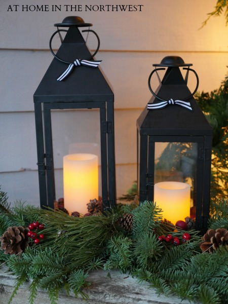 LANTERNS ON FRONT PORCH WITH GREENS AND PINECONES