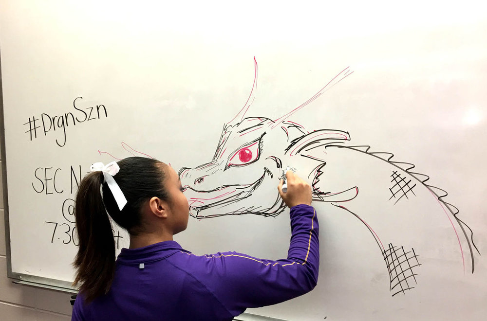 LSU gymnast Erin Macadaeg draws a fire breathing dragon on a whiteboard in the team locker room earlier this season.