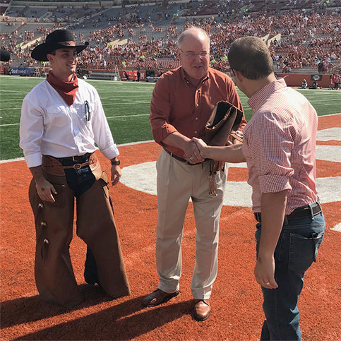 Pictured (from left): Connor Huffman, Foreman – Fall 2017, UT Men's Athletic Director and Cowboy Old Man, Mike Perrin, Texas Cowboys Alumni Assoc. President, Ace Schlameus. The Texas Cowboys presented Cowboys Old Man and UT Men's Athletic Director, Mike Perrin (New Man - 1966) with a pair of chaps in an on-field ceremony prior to the Texas v. Maryland game.