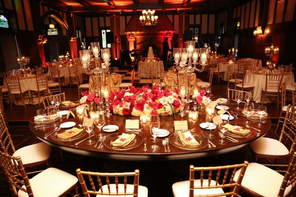 Guest table arrangements featured mounds of hydrangea, garden rose and roses that are surrounded by various levels of stemmed floating candles. The candles provided layers of candlelight.