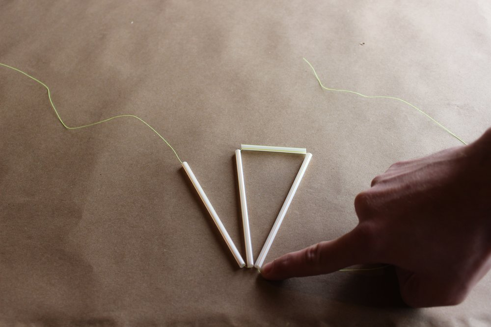 Step 3.) Thread the piece on your left through a 2.5 inch straw and another 5 inch straw forming a triangle between the two longer pieces and one shorter piece. Tie the pieces together at the top tightly.