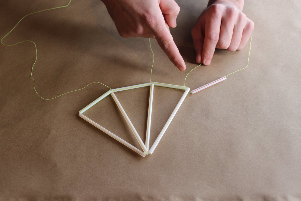 Step 6.) Cut a NEW piece of string about a foot long and thread a 2.5 inch straw. Tie a knot leaving about 4 inches of string where the knot connects.