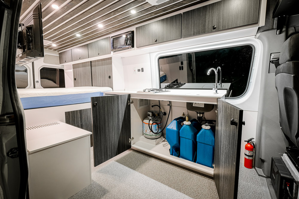 Under-sink storage includes 2 7-gallon jerry cans for fresh water, one for gray/waste water, and a 20-lb propane bottle to feed the two-burner range as well as the rear-mounted shower system.