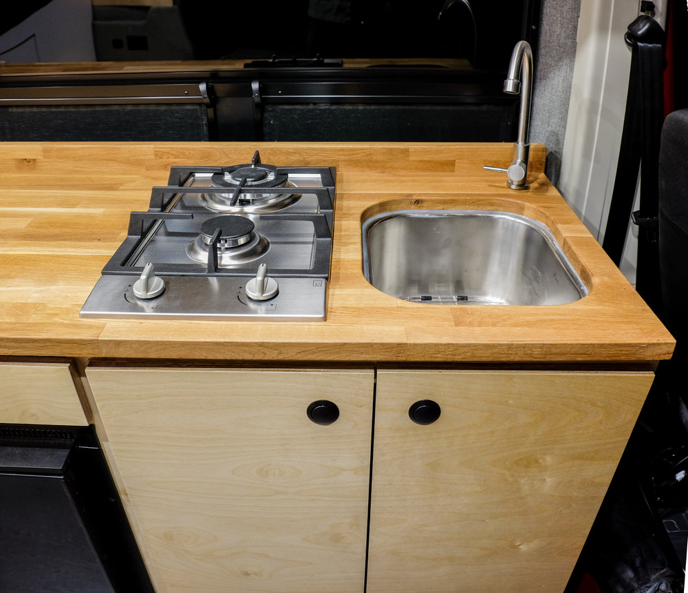Under the kitchenette's oak butcher block countertop is a 7 gallon fresh-to-grey water system and an 11-lb propane tank. The propane fuels the two-burner cooktop as well as the rear-mounted shower system. Above the Isotherm refrigerator is a touch-to-open cutlery drawer. The dual vented window behind the kitchenette allows for some nice airflow (and a great view) while cooking.