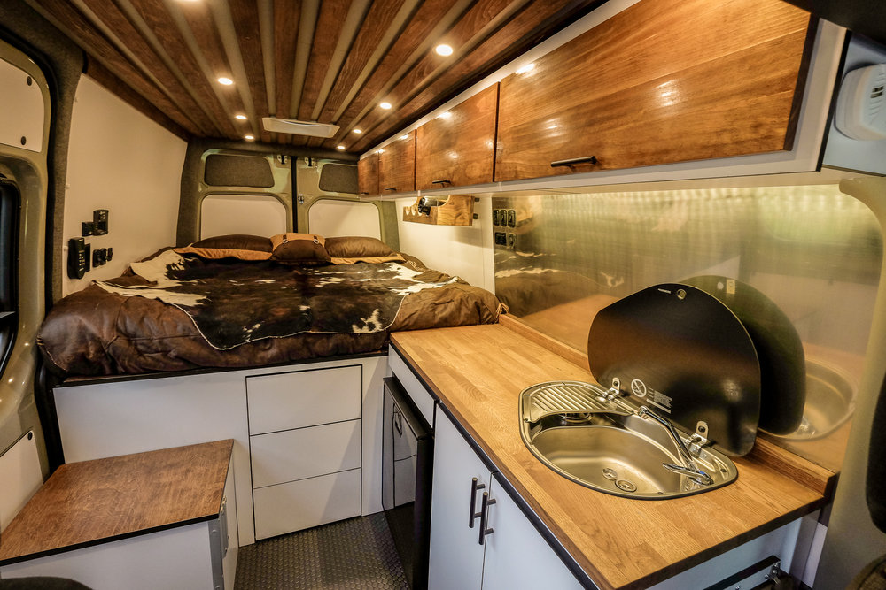 "Vanlife Customs: 144"" Mercedes Sprinter 4x4 campervan conversion interior. Features include: custom wood cabinetry, SMEV cooktop, Isotherm refrigerator, brushed stainless steel backsplash, and custom wine rack."