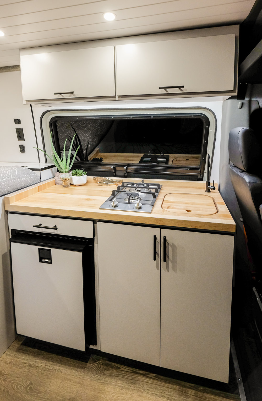 JOMOVAN'S kitchenette is equipped with an  Isotherm 85 Elegance  refrigerator, two burner cook top, a high capacity water filtration system, and a jet black filtered drinking faucet to match the modern aesthetic.