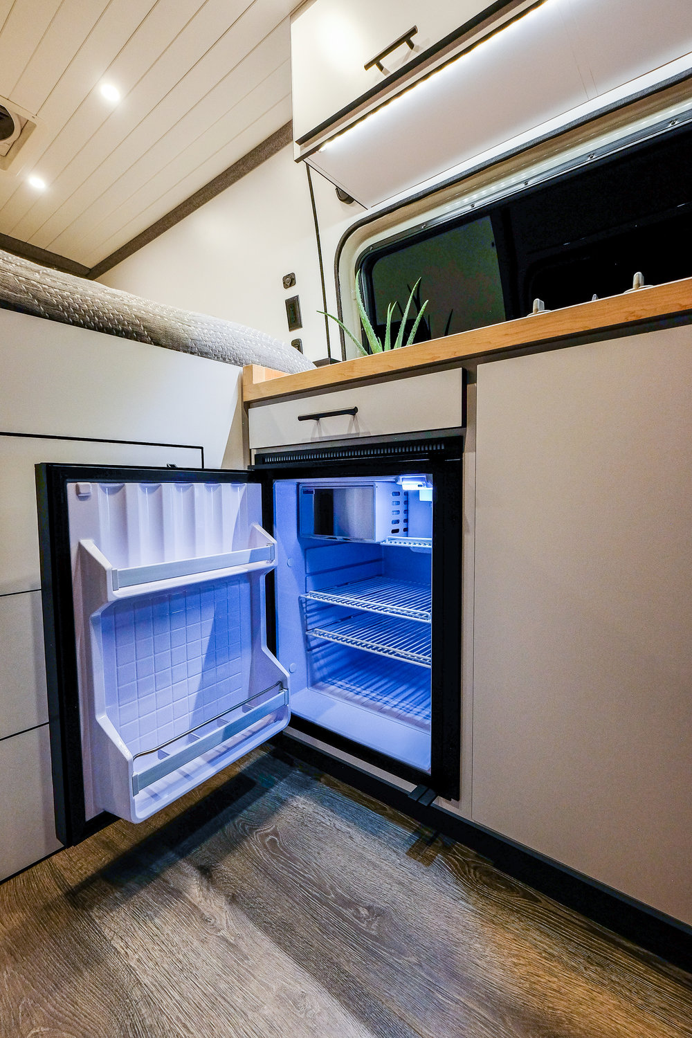 JOMOVAN'S kitchenette is equipped with an  Isotherm 85 Elegance  refrigerator, two burner cook top, a high capacity water filtration system and a jet black filtered drinking faucet to match the modern aesthetic.
