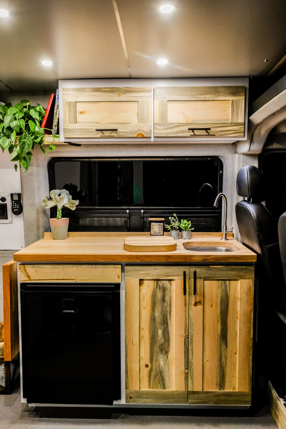 The kitchenette includes an  Isotherm Cruise 85 Elegance  refrigerator, a double burner cooktop and a butcher block counter.