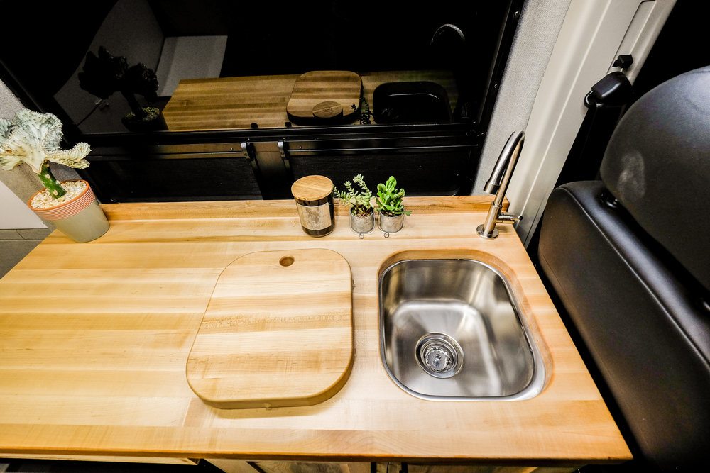 """The 14"""" stainless steel sink is fed by our signature water system and has a butcher block cover which doubles as a cutting board."""