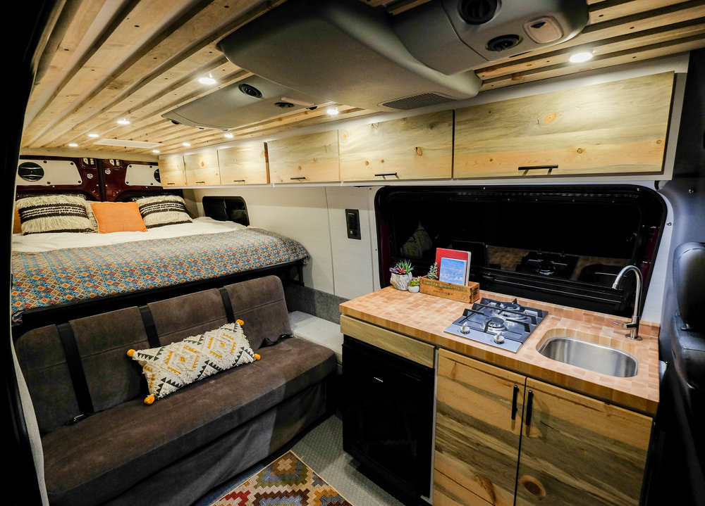 """Maroon Bells: Vanlife Customs 170"""" Mercedes Sprinter 4x4 Camper Van Conversion. Features include: custom beetle kill pine cabinetry, convertible bench-to-bed, Isotherm refrigerator, MaxxAir 7500k fan, Coleman Mach AC unit, custom beetle kill pine slatted ceiling, two burner propane cooktop, RB Components headliner shelf, Lonseal flooring, seat swivels, Espar heater, CR Laurence t-vent windows and Aluminess exterior accessories."""