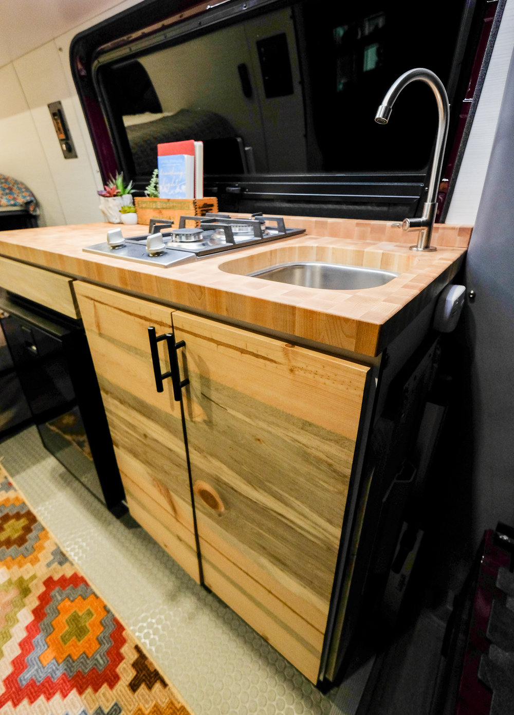 Maroon Bells' kitchenette includes an  Isotherm Cruise 85 Elegance  refrigerator, a double burner cooktop, and a unique zebrawood end grain butcher block countertop.