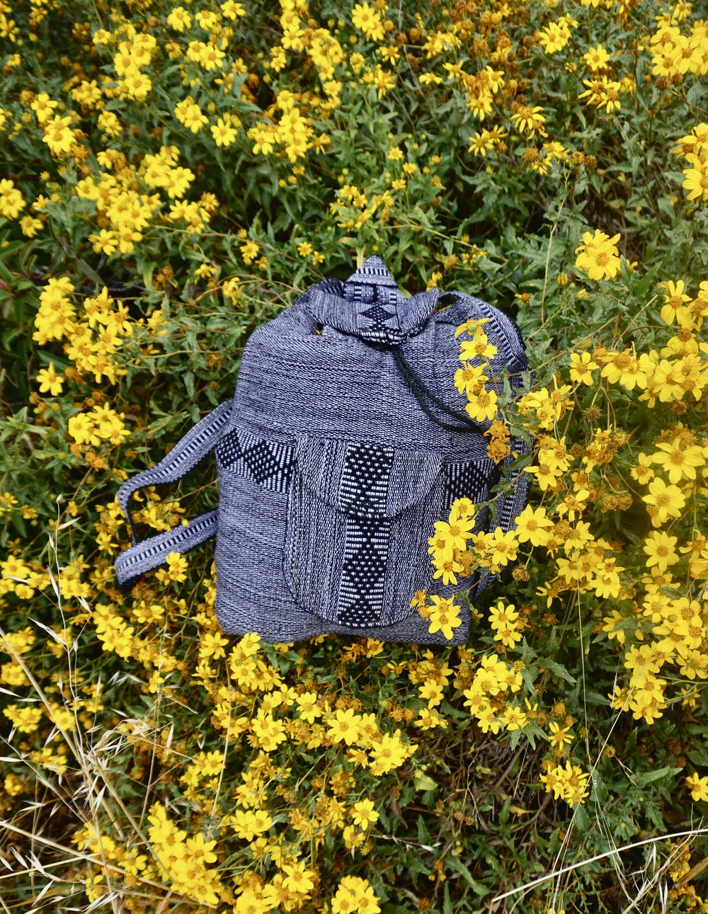 Baja Roots backpacks have a front zipper pocket,a chord on the top and pin to close the bag and keep it closed. They are coming out with a new prototype that will be for water sports and for hiking, I'll keep you informed.