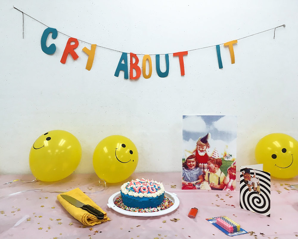 PityParty installation  (2017). Banner made from construction paper and string. Table composed of store bought balloons, candles, confetti, table cloth. Additions include a home baked and hand decorated cake, and screen printed cards.