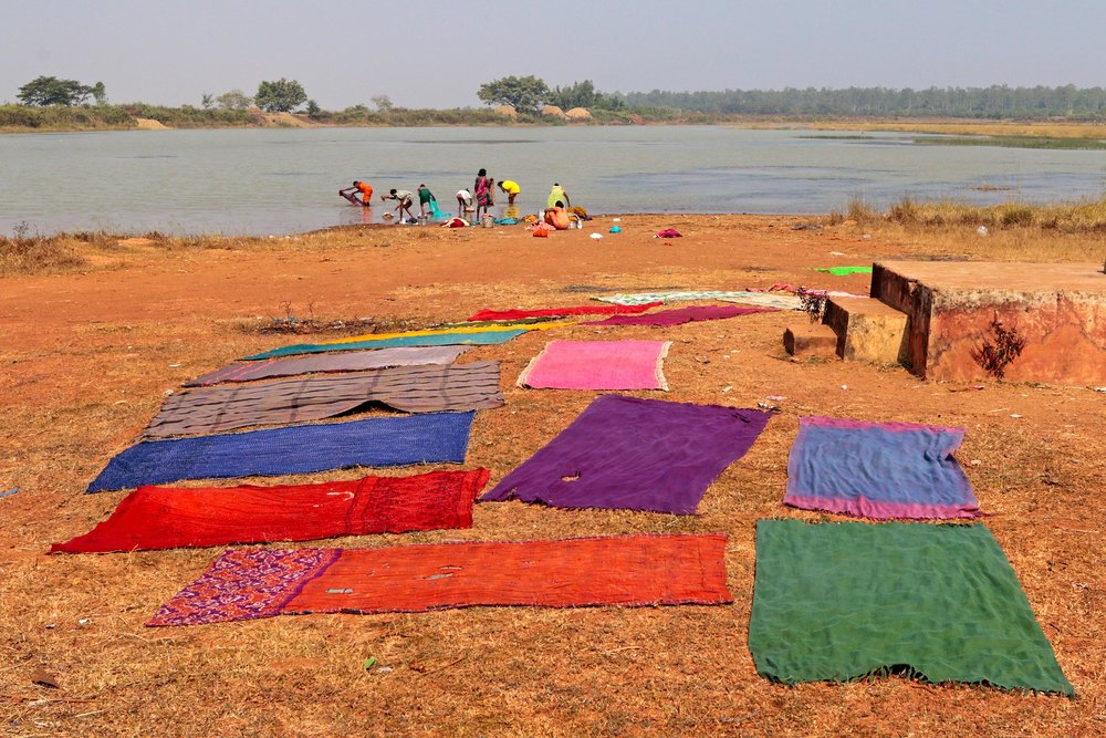 TEXTILES BEING DRIED BY A LAKE IN A VILLAGE IN ORISSA IN SOUTHEASTERN INDIA