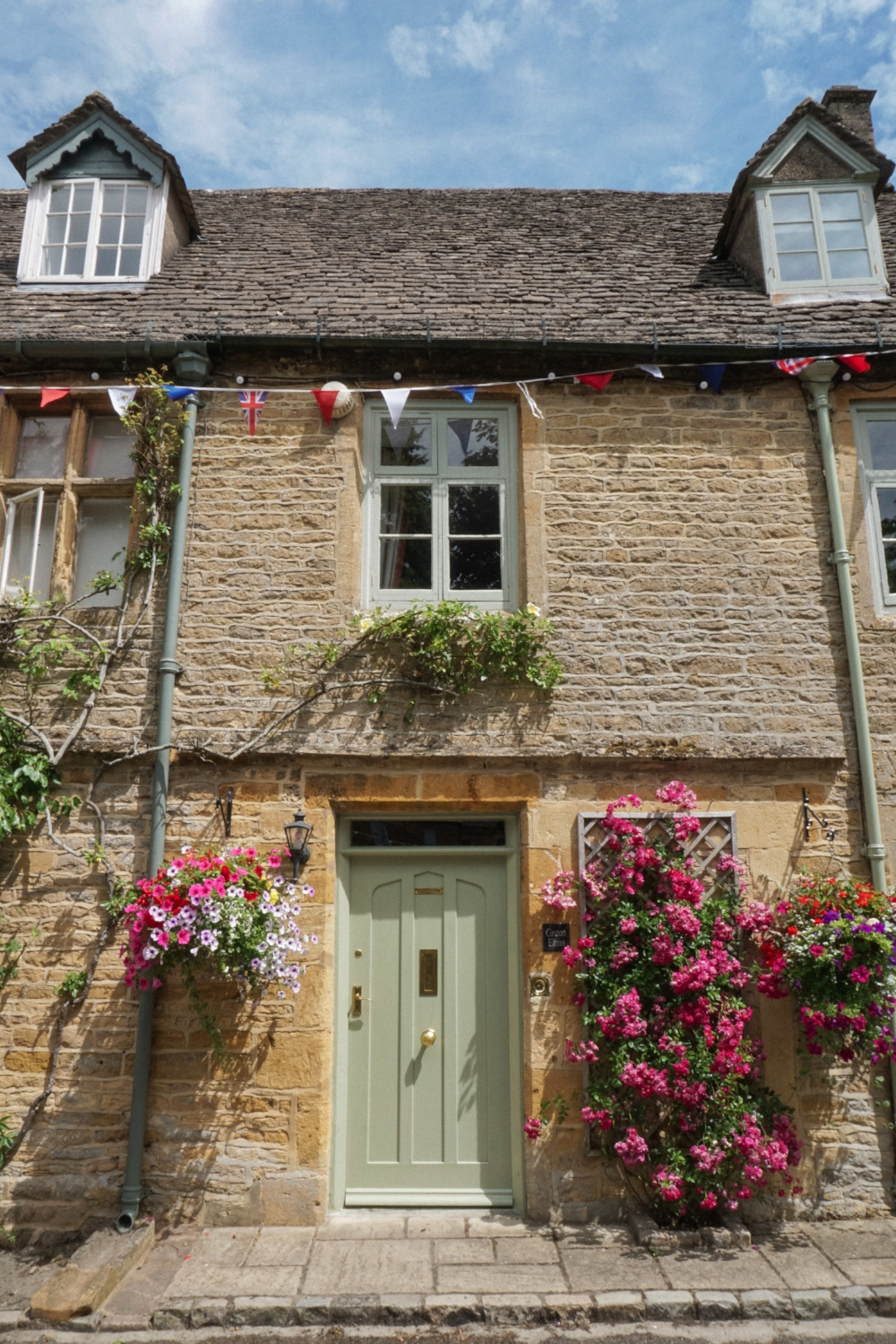 curio.trips.england.cotswolds.house.flowers.bunting.jpg