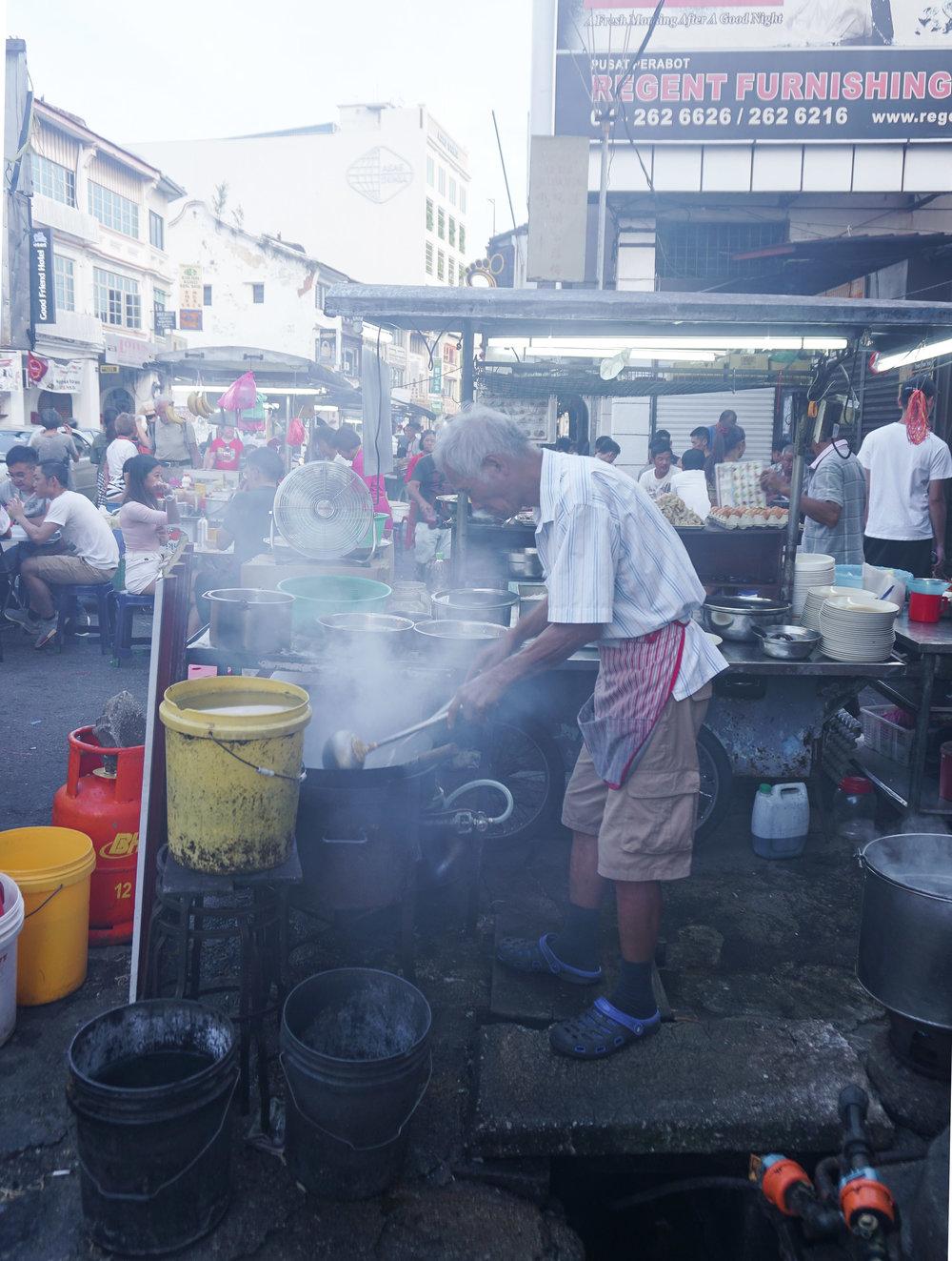 curio.trips.malaysia.penang.night.market.vendor.smoke.portrait.jpg