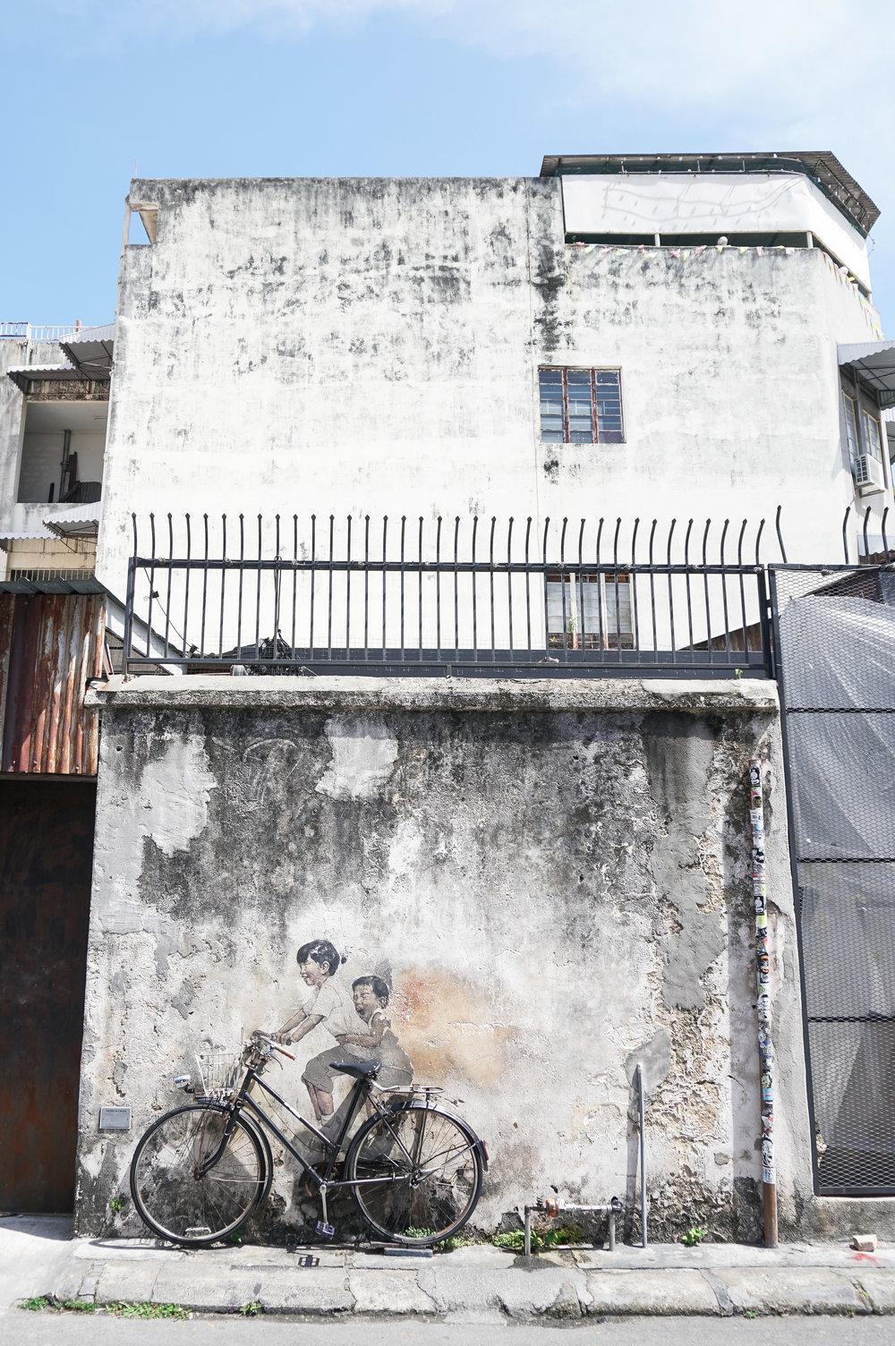 curio.trips.malaysia.penang.street.art.girl.boy.bike.portrait.jpg